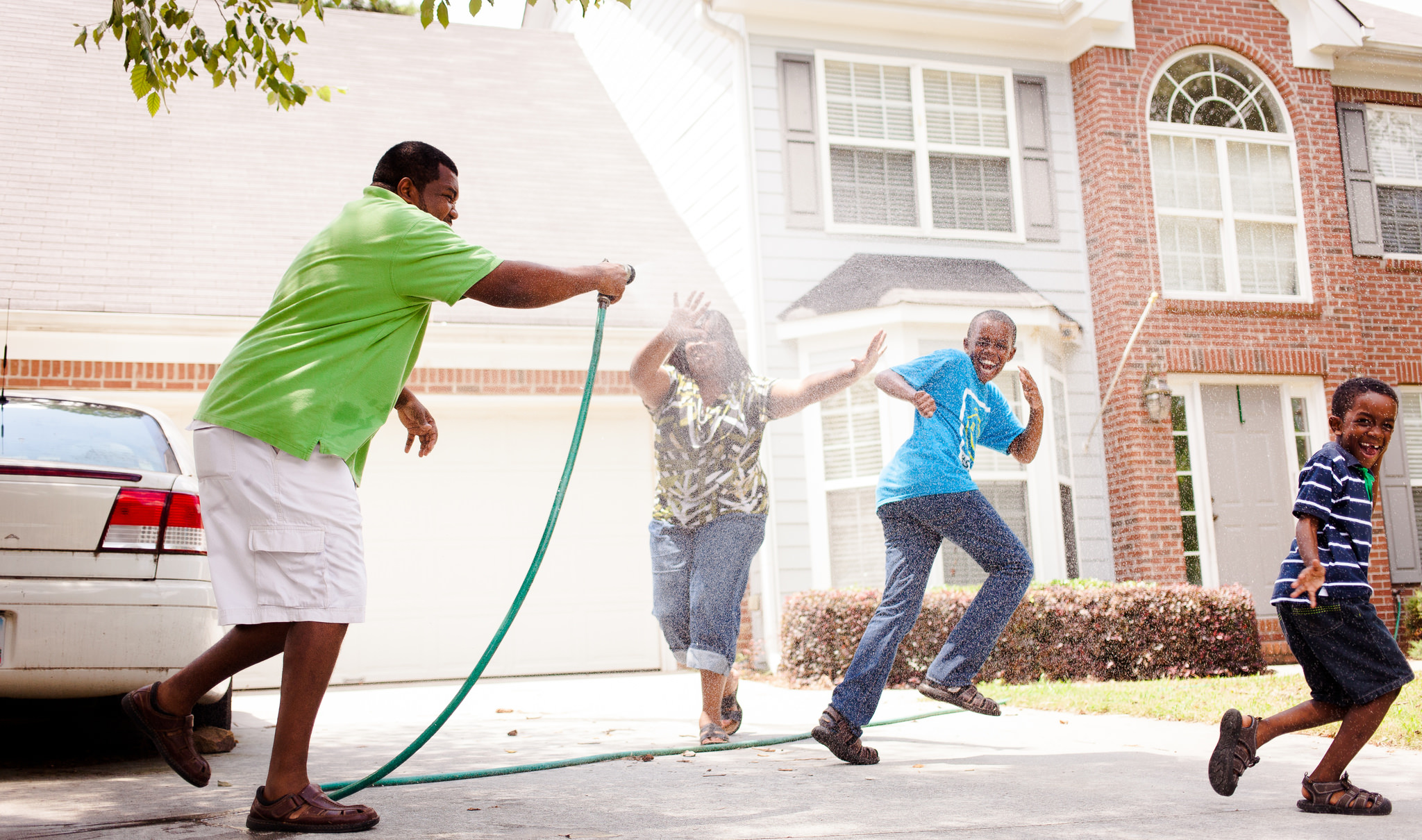 Father plays with his boys using a hose.